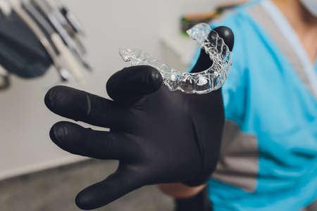Close-up Of A Womans Hand Putting Transparent Aligner In Teeth.