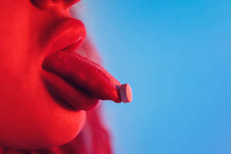beautiful girl with lsd on tongue in nightclub with pink smoke.
