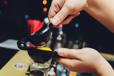 Close-up image of a barman hands squeezes lemon juice into a chilled shaker on the bar counter.