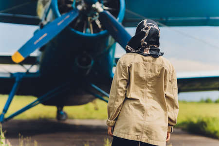 a young Muslim woman in a headscarf stands against the background of an old plane. Standard-Bild