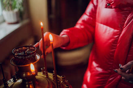 Womans hand in a red jacket puts a church candle.