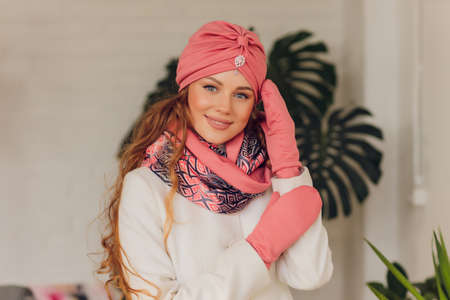 happy beautiful woman looking sideways in excitement. girl wearing knitted warm hat and mittens.