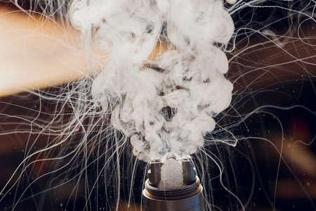Splash glicerine on vape spiral. Big clouds of fog with visible tracers. Vape culture and no smoking. Foto de archivo
