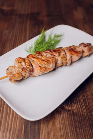 Chicken kebabs on wooden background, top view.