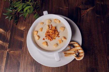 Mushroom soup in white pots, on napkin, on wooden background.