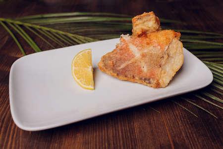 Beautifully fried pieces of carp on a black plate. Фото со стока
