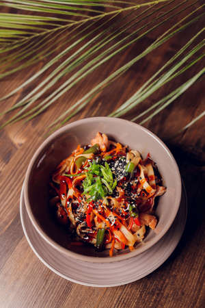 Appetizing asian cuisine chicken and vegetables udon noodles wok on the wooden table, horizontal.