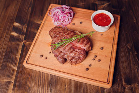 Beef steak with twig rosemary on a wooden table.