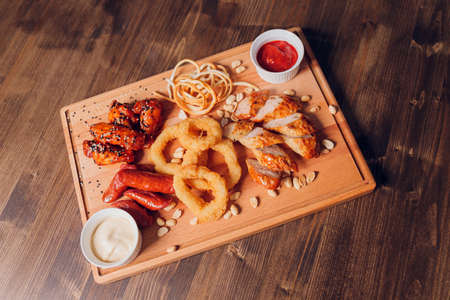 wide selection of snacks for beer with different sauces on parchment top view.
