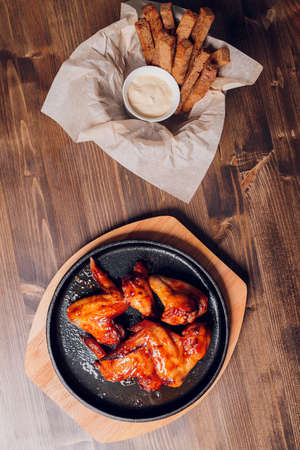 Chicken wings on white plate with sauce on wooden table. Low angle.