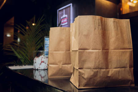dessert paper bag waiting for customer on counter in modern cafe coffee shop, food delivery, cafe restaurant, takeaway food, small business owner, food and drink concept.
