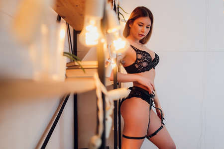 Extremely beautiful and young adult caucasian woman wearing lingerie in a boudoir bedroom setting in various poses.