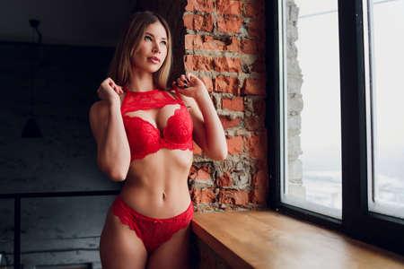 Pretty smiling girl underwear portrait near the window.