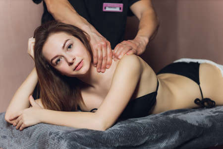 An attractive caucasian woman lying down on a massage bed at a spa. Standard-Bild
