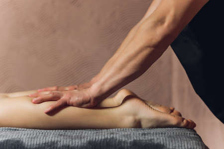 A foot massage being carried out in a spa by a masseuse.