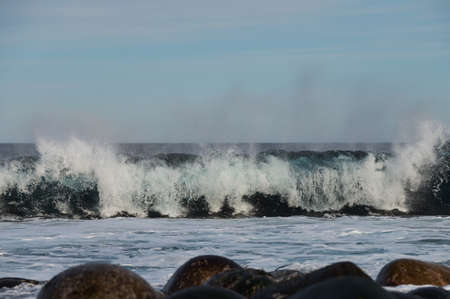 Small sea waves break against the stones of the shore. A bright sunny day and white foam of the waves. Melting glaciers as an environmental impact of air pollution.