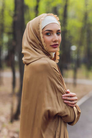 Islamic beautiful woman in a Muslim dress standing on a summer park street background forest autumn trees.world hijab day. Stock Photo