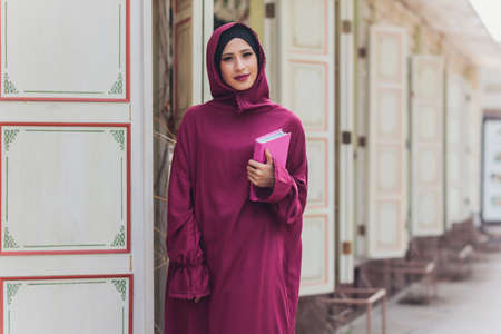 Confident Arab businessman smiling and walks of Dubai. Arab Business vumen hijab is in the streets against the skyscrapers of Dubai. The woman is dressed in a black abaya.