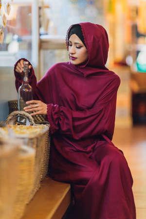 Arabian young muslim woman sitting in a cafe.