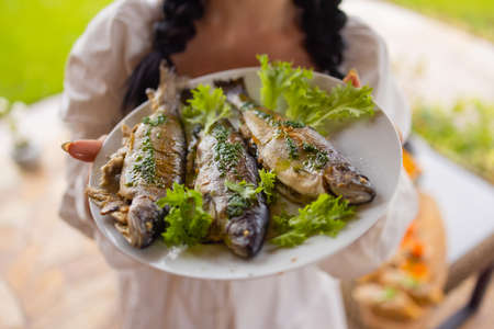 A lot of smoked fish on the table close-up in a plate. Stock fotó