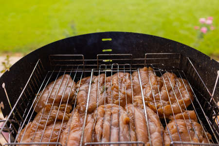 Marinated grilled chicken on the flaming grill.