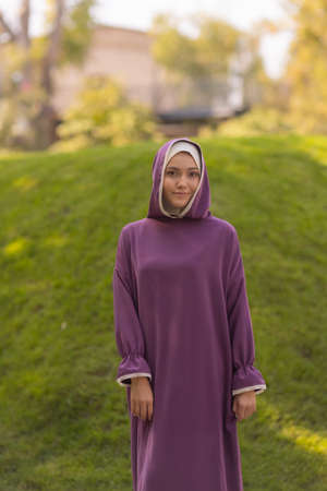 Islamic beautiful woman in a Muslim dress standing on a summer park street background forest autumn trees.world hijab day.
