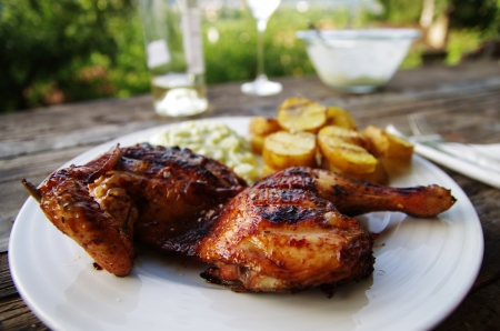 Grilled chicken with potatoes on rustical table outdoors photo