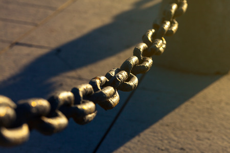 chain fence: Old Rusty Chain Fence On The Street Under Sunshine. Urban Scene Stock Photo
