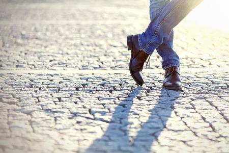 hombres negros: Piernas de hombre en pantalones vaqueros de mezclilla y botas de cuero al aire libre. Foto Fashion Street. Foto de archivo