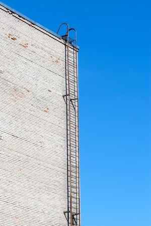 white brick: Metallic Ladder On White Brick Wall. Sky Background. Success Concept Stock Photo