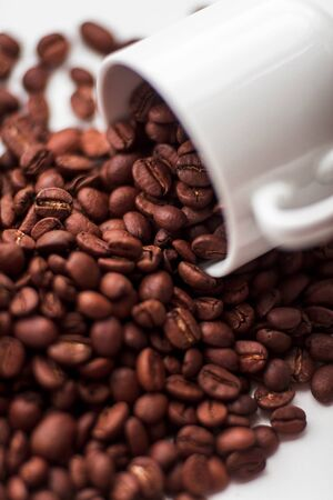 Scattered coffee beans and cup on white windowsill. Morning breakfast concept background Stock fotó