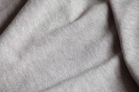Wool fabric texture close up background. Cozy style cloth. Wavy folds material