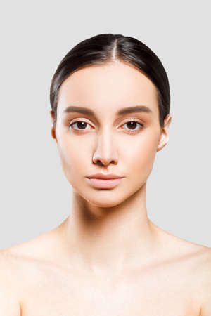 Beautiful woman face closeup studio portrait. Young attractive model girl. Perfect skin.