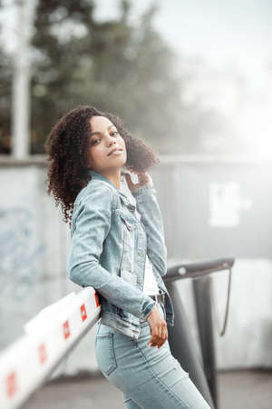 Mulatto black curly girl on street. Sunny summer city. Young woman denim style