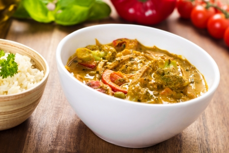 Yellow hot curry dish with mixed vegetables served in a white small bowl  Stock Photo