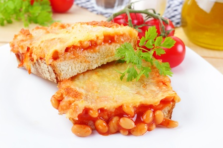 nack: baked beans on fresh bread with grated cheese and herbs  Stock Photo