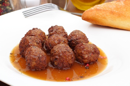 tasty meatballs in a spicy sauce with fresh bread photo