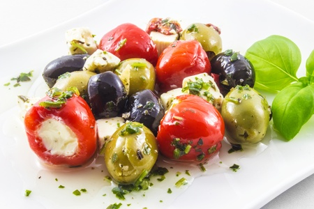 Mixed antipasti plate  Olives and peppers filed with creamcheese and feta cheese  Stock Photo
