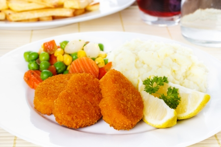 Chicken nuggets with mashed potatoes and vegetables photo