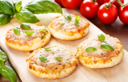 homemade vegetarian mini pizzas served on a wooden board