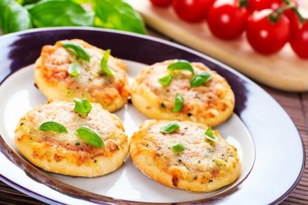 Hausgemachte vegetarische Mini-Pizza serviert auf einem Holzbrett Standard-Bild - 23025175
