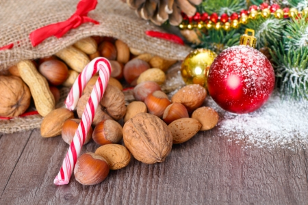 walnuts, peanuts and hazelnuts in a jute bag with christmas decoration in the background  photo