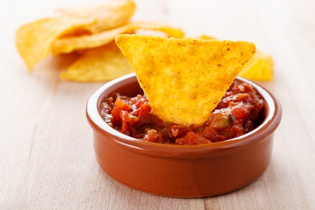 fried tortilla chip with a hot tomato salsa dip