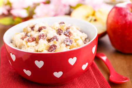 creamy rice pudding with cinnamon, apple pieces and raisins