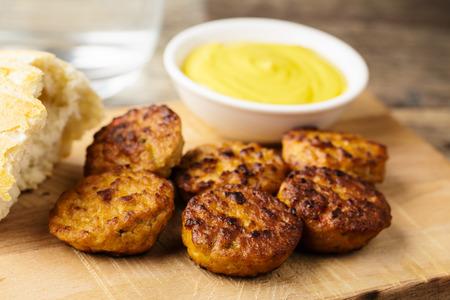 beefsteak: hearty beefsteak bites with mustard served on a cutting board.