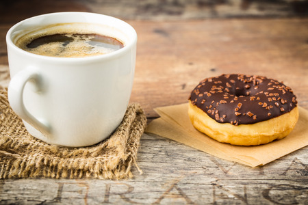 tasty donut with nut-chocolate topping and  fresh brewed coffee photo