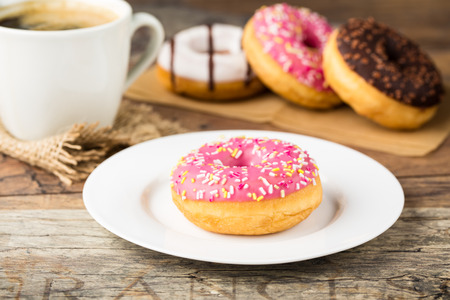 tasty donut with sprinkles and  fresh brewed coffee photo