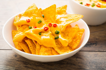 close up food: spicy tortilla chips with cheese and chili peppers.