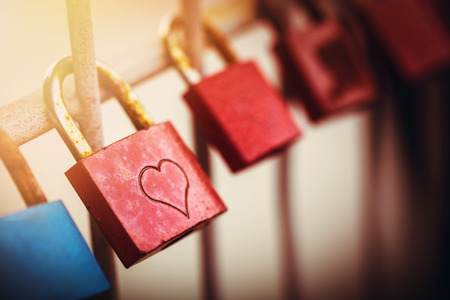amorousness: some love padlocks at a bridge while sundown