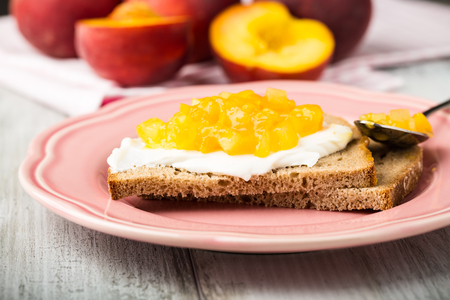 sandwich spread: 2 pieces of bread with cream cheese and stewed yellow fruits. Stock Photo